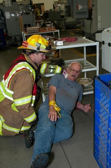 Firefighter tending to man lying on floor