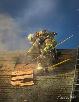 Fire fighter breaking through  roof shingles - with billowing smoke rising from the hole